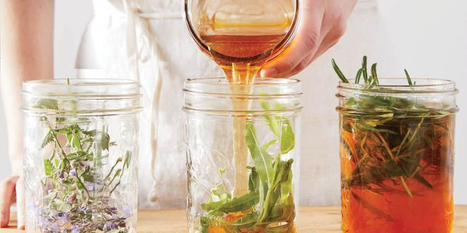 A woman in a white apron pouring honey into jars of herbs.